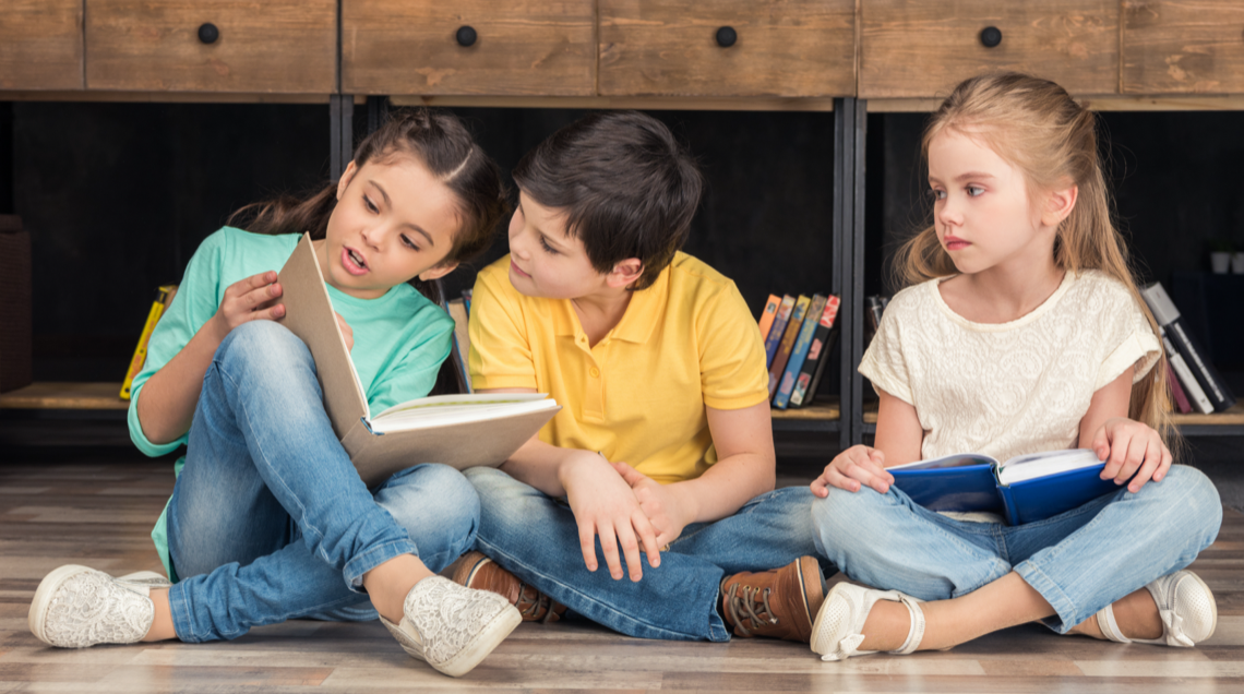 elementary school girl looks troubled as she watches two classmates reading to each other