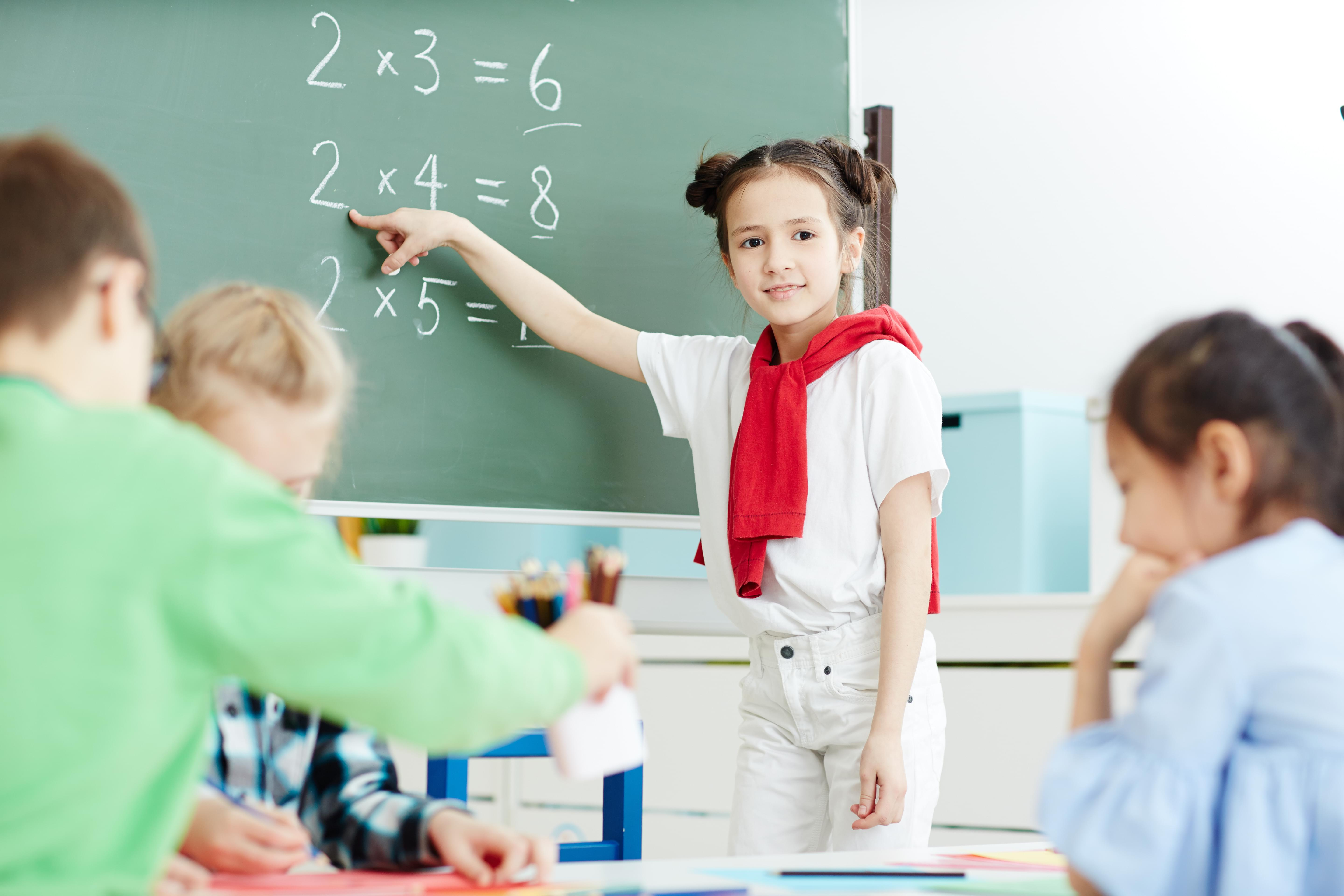 elementary school age student looking at chalk board with multiplication tables