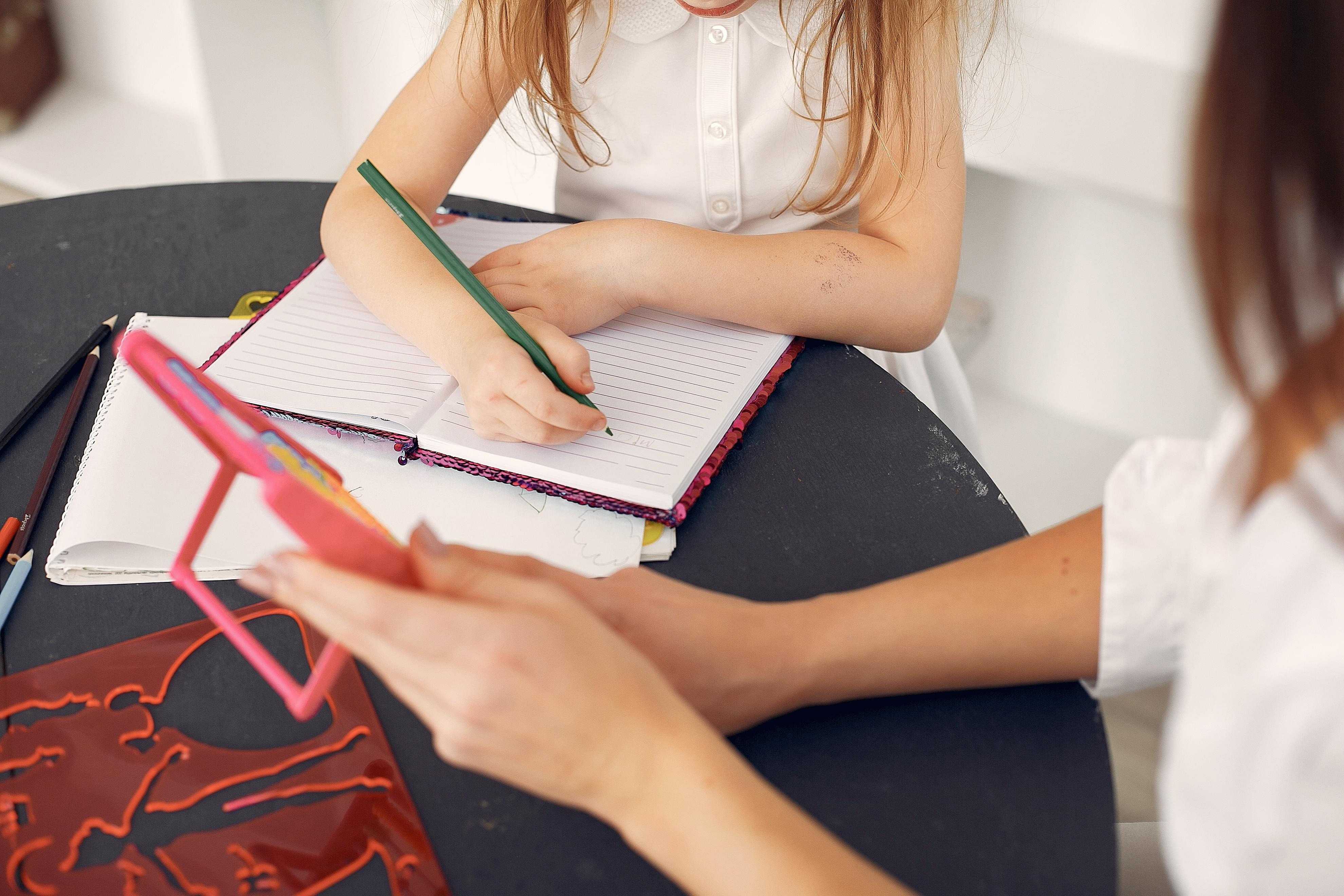 elementary school child and tutor writing in notebook
