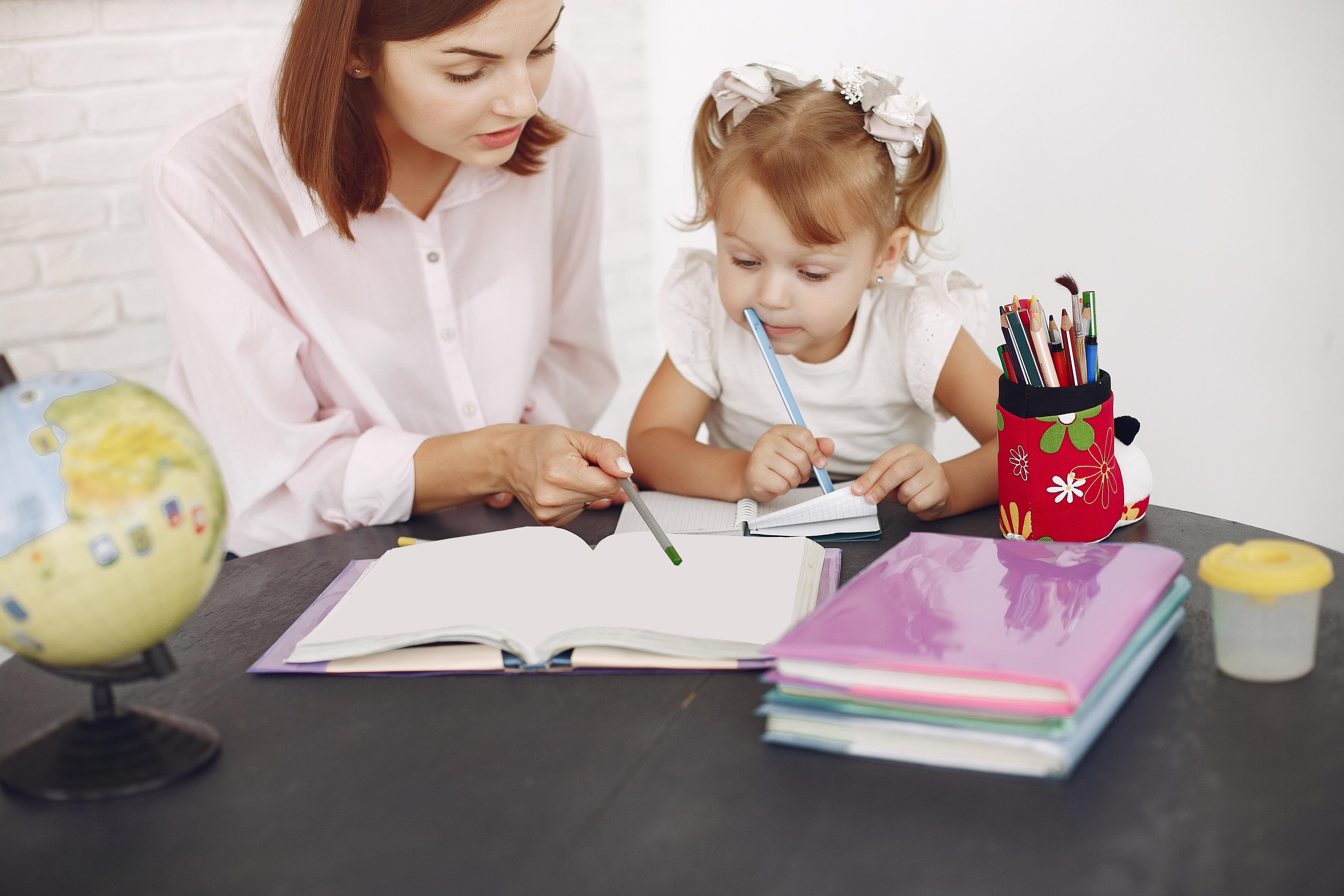 pre kindergarten child and tutor looking and pointing at notebook