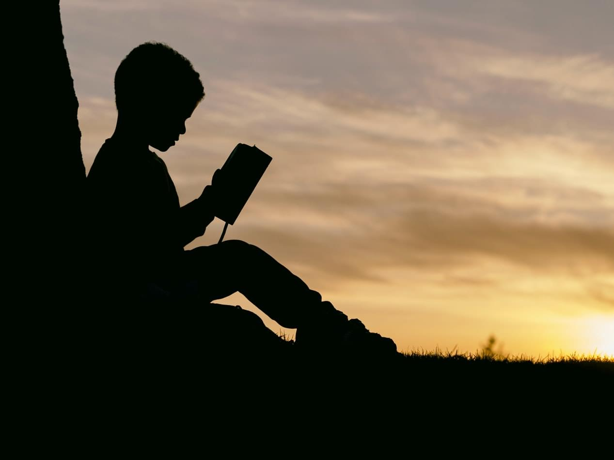 child reading sitting against a tree