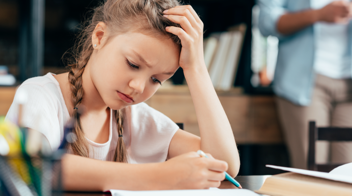 elementary school girl looking frustrated with head on hand doing homework