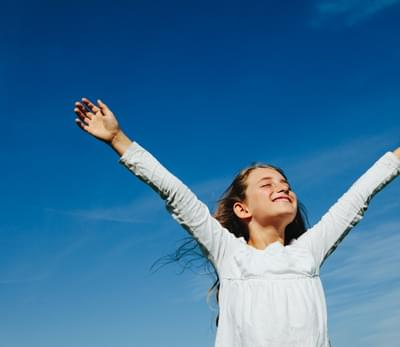child with arms up and blue sky