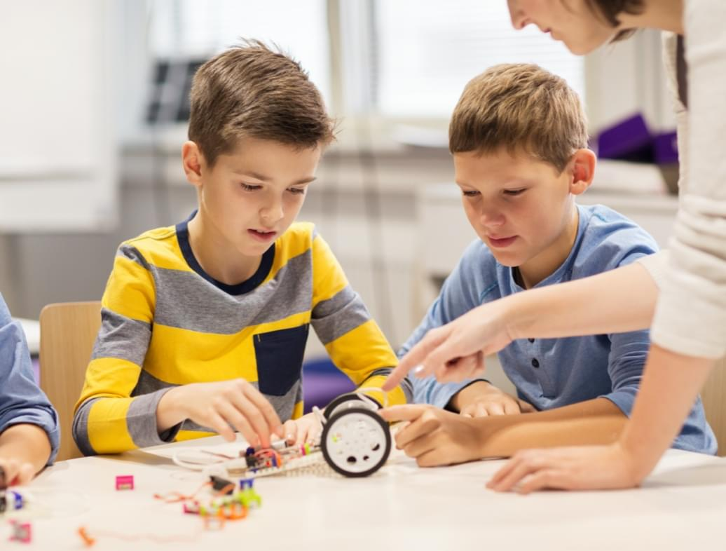 two student and a teacher looking at science model