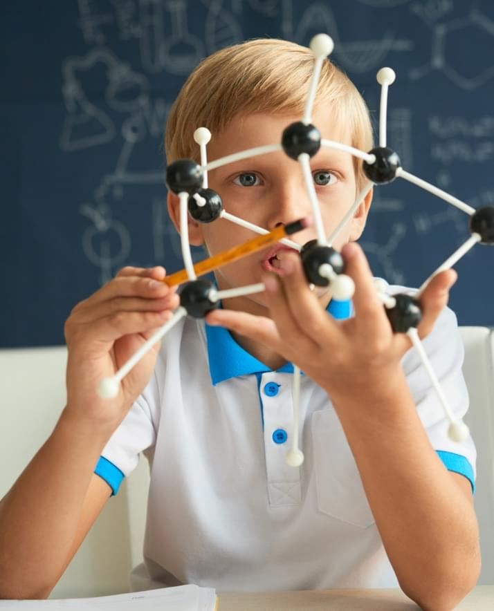 young student holding science molecule model