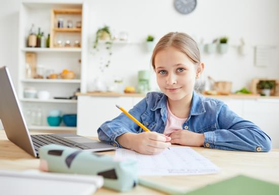young student studying next to computer